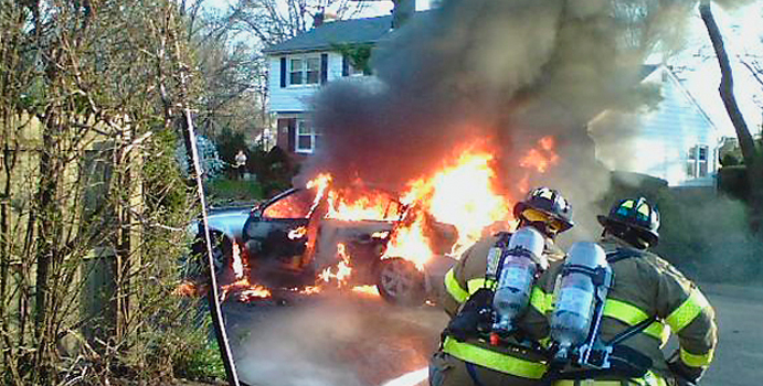 Firefighters fight a car fire